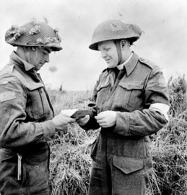H/Captain Robert L. Seaborn, Chaplain of the 1st Battalion, The Canadian Scottish Regiment, distributing New Testaments near Caen, France, 15 July 1944.