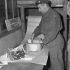 Private Leon Biron of No.1 Army Base Post Office, Canadian Postal Corps (C.P.C.), rewrapping damaged parcels, Dieppe, France, 11 October 1944.