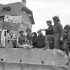 Infantrymen of Le Régiment de la Chaudière talking with French civilians, Bernières-sur-Mer, France, 6 June 1944.
