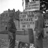 """Two unidentified Canadian non-commissioned officers reading a sign which states, """"This is a 2 Div Town - Behave Yourselves In It"""", Dieppe, France, 9 September 1944."""