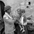 Trooper Ralph Catherall of The Calgary Regiment giving food to an Italian child, Volturara, Italy, 3 October 1943.